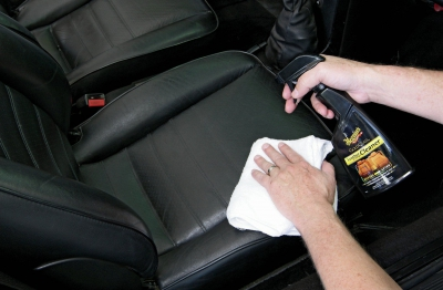 Cleaning a car seat with spray and cloth